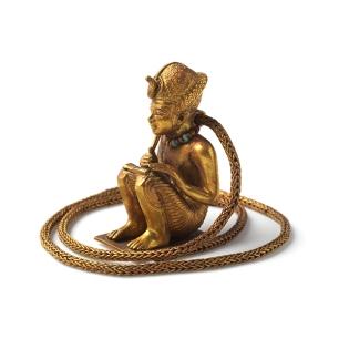 Figurine prosternée et chaine en or représentant un roi accroupi.